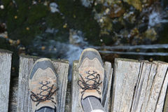 hiking shoes of a hiker on the wooden bridge Royalty Free Stock Photo