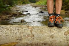 Hiking shoes legs on trunk on mountain trail. Hiking shoes legs on tree trunk, mountain trail. Man hikers hike boots in closeup with mountain river in the Stock Image