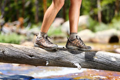 Hiking shoes - man hiker balancing crossing river. Hiking man crossing river in walking in balance on fallen tree trunk in nature landscape. Closeup of male Stock Photography