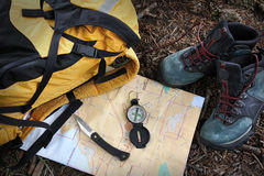 Hiking shoes on map with compass Royalty Free Stock Photo