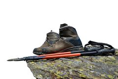 Hiking shoes and Nordic walking poles on the rock. Royalty Free Stock Photography