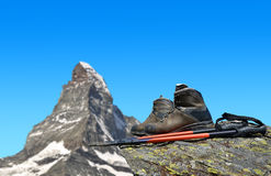 Hiking shoes and poles on the rock Stock Images