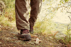 Hiking shoes with red laces and legs wearing long brown trousers royalty free stock image