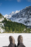 Hiking shoes on with snowy mountains in the background. Royalty Free Stock Photos