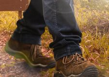 Hiking shoes walking in wild rough nature grass Royalty Free Stock Photo
