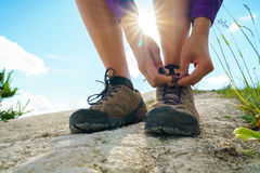 Hiking shoes - woman tying shoe laces. Closeup of female tourist getting ready for hiking Royalty Free Stock Photos