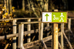 Hiking sign with distance 3 km. Hiking sign with distance in front of the bridge Royalty Free Stock Photos