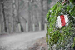 Hiking sign on a moss rock. Red band hiking sign on a moss rock Stock Photo