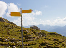 Hiking signpost and guesthouse, Switzerland. Summer mountain landscape with hiking signpost, meadows and guesthouse, concept for directions, Switzerland stock image
