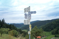 Hiking signs in the Black Forest, Germany. White directional signs on the West hiking trail in the Black Forest, red rhombus as an advice for hikers, in the Royalty Free Stock Photos