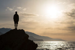 Hiking silhouette backpacker, man looking at ocean Stock Photo