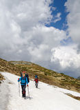 Hiking in spring mountains. Two tourists with backpacks go on a snowy field. The sky is cloudy Stock Image