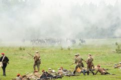 Hiking squad lying on grass and shoot. RUSSIA, CHERNOGOLOVKA - MAY 17: Kornilovs hiking squad lying on grass and shoot  on History reenactment of battle of Civil Royalty Free Stock Photography
