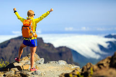Hiking success, happy woman in mountains. Hiking woman and success in mountains. Young female backpacker celebrating on mountain top. Fitness and healthy Royalty Free Stock Photography