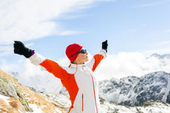 Hiking success, woman in winter mountains. Hiking woman and success in mountains, arms outstretched. Female fitness and healthy lifestyle outdoors in winter Royalty Free Stock Photography