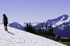 Hiking Summer Snow. A female hiker crosses a snow patch high in the mountains during summer months Stock Images