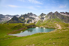 Hiking in swiss alps. Hiking in the swiss alps: family relaxing after reaching summit Stock Image