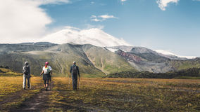 Hiking Team Goes To Mount Elbrus, Rear View. Travel Destination Experience Lifestyle Concept concept. A team of travelers with backpacks and trekking sticks goes Royalty Free Stock Images
