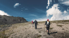 Hiking Team. Travel Destination Experience Lifestyle Concept concept. A team of travelers with backpacks and trekking sticks climbs the mountain stock photo