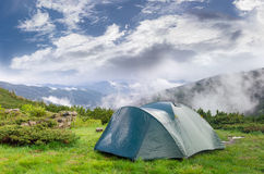 Hiking tent after rain on background of mountains and sky Royalty Free Stock Photo