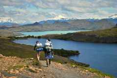 Hiking to the lake. Picture of people hiking in Torres del Paine National Park, in southern Chile, during a cloudy day with the Nordenskjold lake and snowy royalty free stock photography
