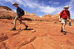 Hiking to The Wave. Two hikers walk along sandstone en route to The Wave in the Coyote Buttes section of the Paria Canyon-Vermilion Cliffs Wilderness in northern Royalty Free Stock Image