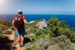 Hiking tourist man in front of beautiful seascape. Hiker trekking with backpack on rocky trail path. Healthy fitness lifestyle. Outdoors concept on royalty free stock photos