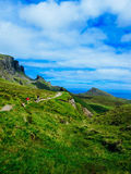 Hiking tourists on Isle of Skye. A view of tourists hiking up a path among the rolling green hills on the Isle of Skye in Scotland Stock Photo