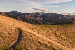 Hiking track across grassy slopes Stock Photos