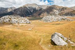 Hiking track leading to Castle Hill limestone rock formation in New Zealand. Hiking track leading to Castle Hill limestone rock formation in Southern Alps, New stock photography