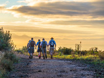Hiking trail. A group of men hiking in the countryside on a clear autumn morning as the sun rises to brighten the sky stock photo