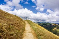 Hiking trail through the hills of south San Francisco bay area; closed cattle gate blocking the trail; San Jose, California royalty free stock photography