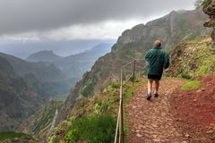 Hiking on the trail in Madeira. Senior tourist in the mountains of Madeira at Pico do Areeiro Arieiro, while hiking to Pico Ruivo on a cloudy summer day with stock photos