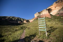 Hiking trail in mountains at Golden Gate. Hiking trail path up steep hill towards golden mountain range with signs showing trail paths at Golden Gate Nature royalty free stock image