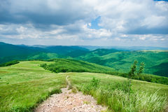 Hiking trail in mountains landscape Stock Images