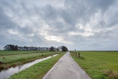 Hiking trail next to the meadow with Stratus Clouds. In the north of the Netherlands, this hiking trail is next to the meadow with Stratus Clouds on a rainy day Stock Image