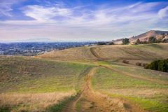 Hiking trail over the hills of Garin Dry Creek Pioneer Regional Park at sunset. Oakland and San Francisco skyline in the background, California stock image