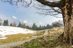 Hiking trail reaches mountain hut. Great view to snow-covered mountains. Hiking trail leads to a wooden mountain hut in the bavarian alps. Great view to snow Royalty Free Stock Images
