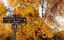 Hiking trail sign. With yellow autumn foliage royalty free stock photos
