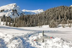 Hiking trail signpost sticks out of deep snow in mountains winter landscape on sunny day. Allgau, Bavaria, Germany. Royalty Free Stock Images