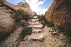 Hiking trail with steps to Arch Rock in Joshua Tree National Park, surrounded by giant boulders.  royalty free stock images