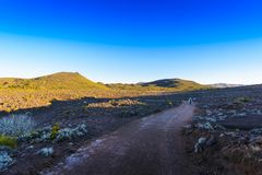 Hiking trail during sunrise at volcanic area of Reunion Island Stock Image