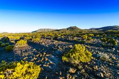 Hiking trail during sunrise at volcanic area of Reunion Island Stock Photos