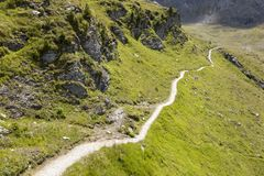 Hiking trail in the swiss alps, Grisons, Switzerland. Hiking path through a green landscape in the swiss alps, Grisons, Switzerland Royalty Free Stock Images