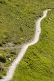 Hiking trail in the swiss alps, Grisons, Switzerland. Hiking path through a green landscape in the swiss alps, Grisons, Switzerland Stock Image