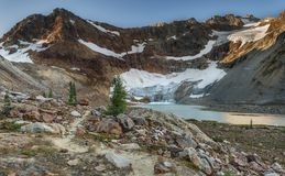 Glacier Recedes into Beautiful Alpine Lake at Dawn. The Hiking Trail to Upper Lyman Lake, Lyman Glacier, and Red Mountain Wake in the Morning with Early Dawn Royalty Free Stock Photos