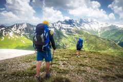 Hiking trail with tourists in mountain range. Trekking in mountains. Two hikers hike on snowy highlands stock photo