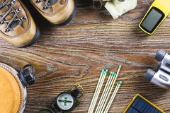 Hiking or travel equipment with boots, compass, binoculars, matches on wooden background. Active lifestyle concept. Top view stock image