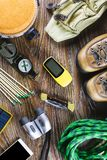 Hiking or travel equipment with boots, compass, binoculars, matches on wooden background. Active lifestyle concept Stock Photos