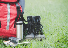 Hiking travel gear on glasses. Items include hiking boots, cup, map,binoculars. Royalty Free Stock Image